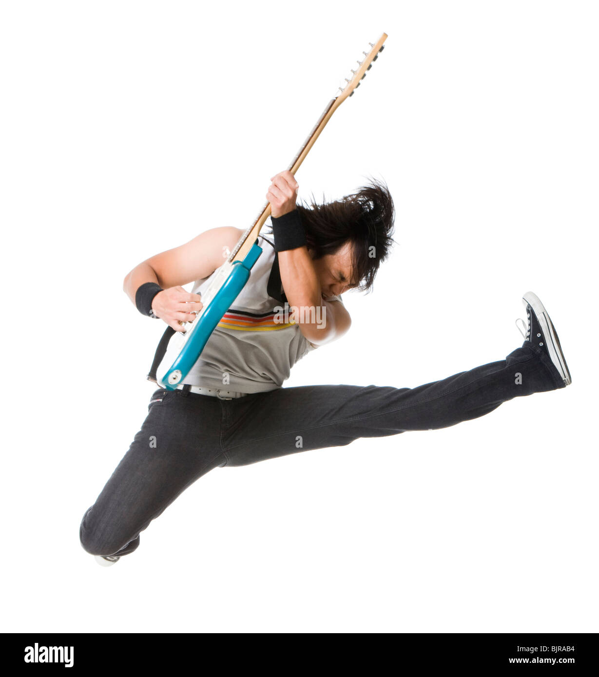 Young man jumping and playing guitar, studio shot - Stock Image