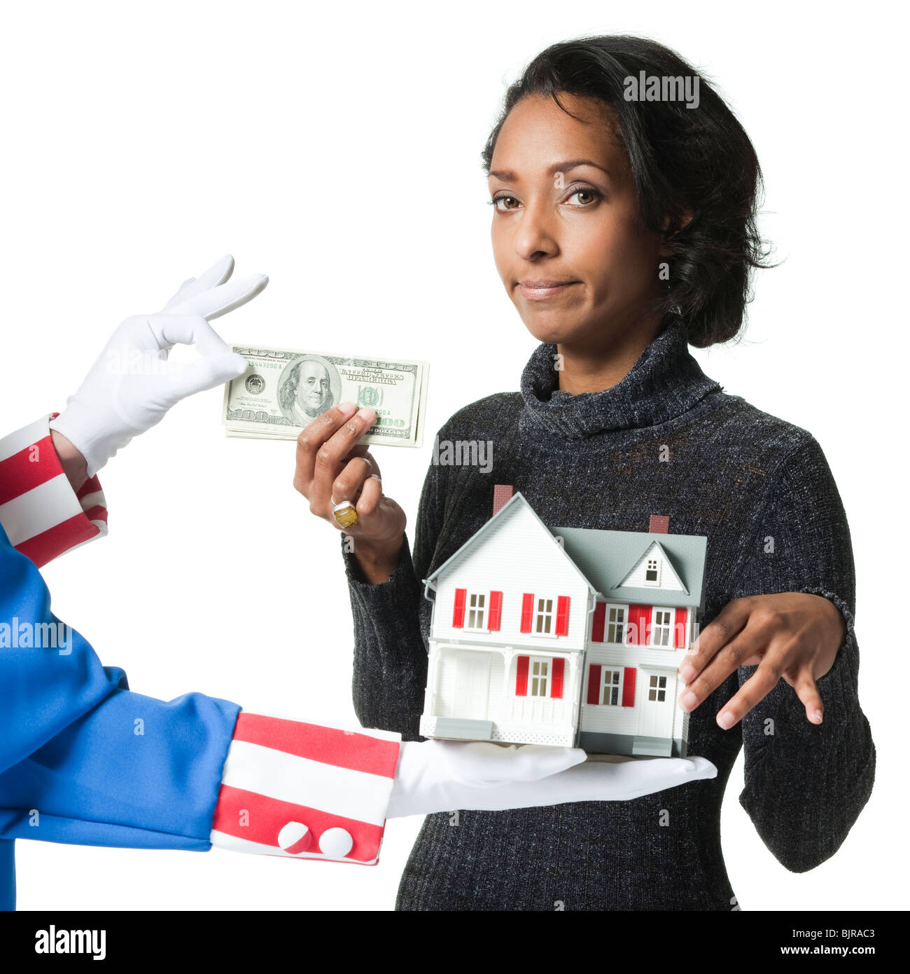 Mid adult woman holding model house and paying for it, studio shot - Stock Image