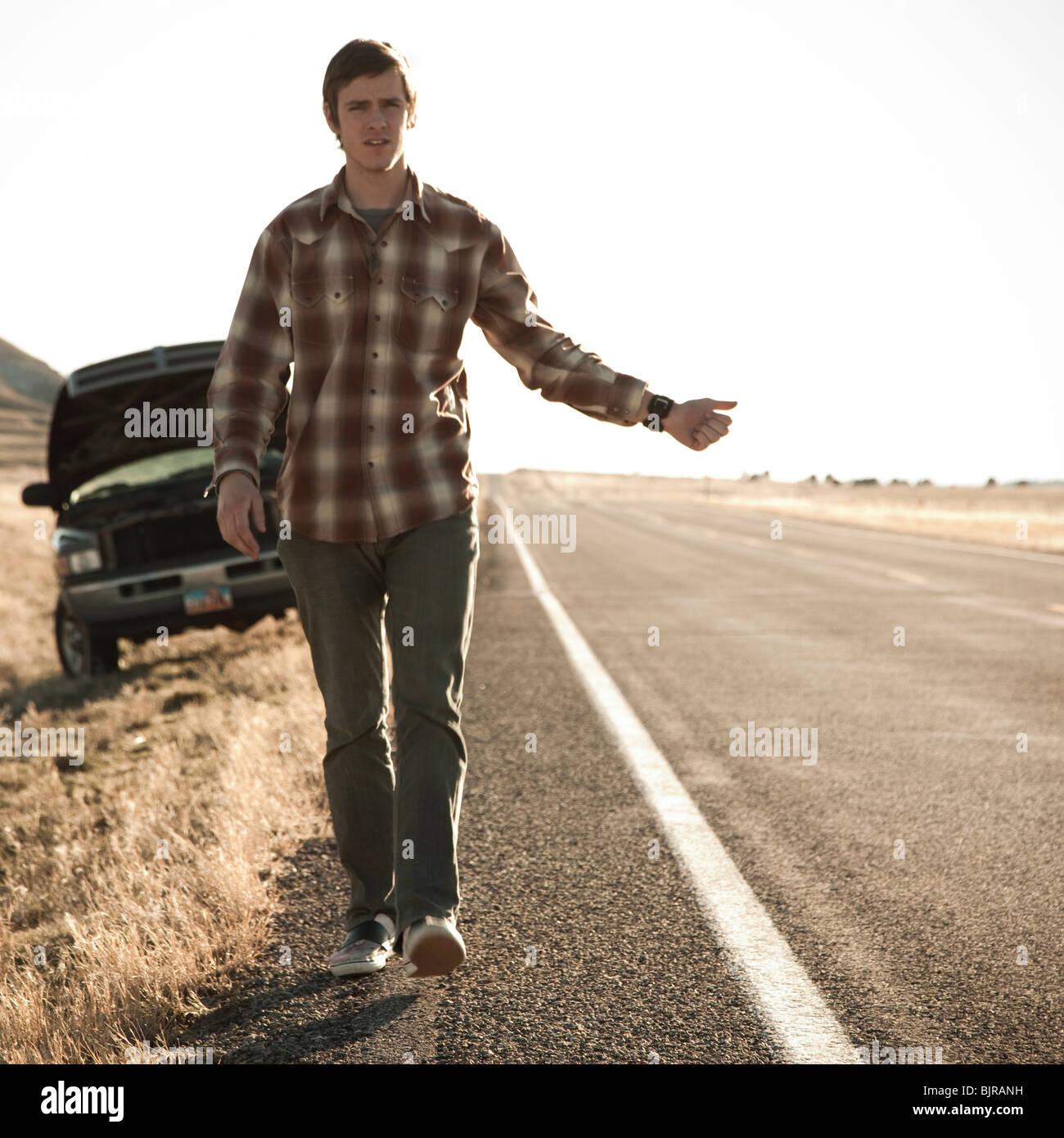 USA, Utah, man hailing on road, broken car in background - Stock Image