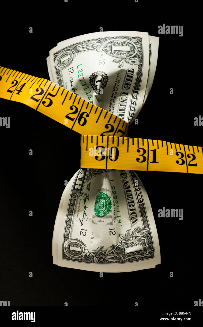 One dollar banknotes tied up with measuring tape against black background - Stock Image
