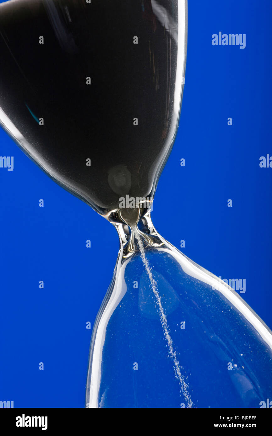 Close-up of hourglass on blue background - Stock Image