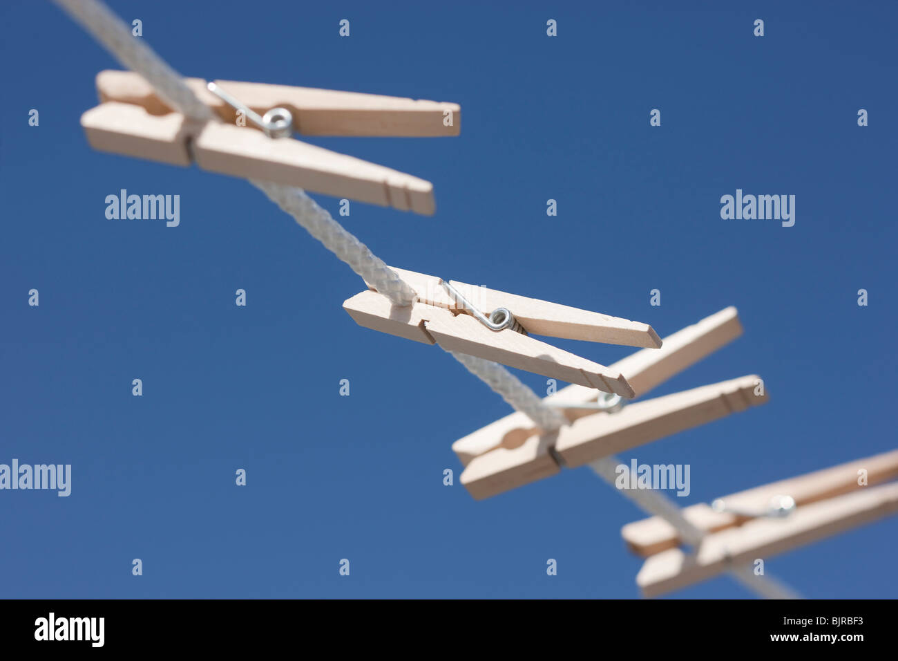 Clothes pegs hanging on washing line - Stock Image