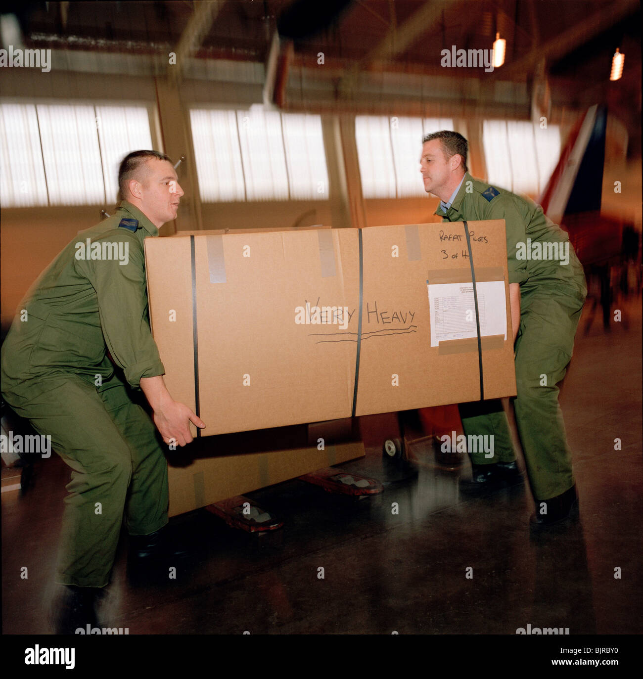 Red Arrows support personnel (Called The Blues) manhandle heavy tri-pack box containing aerobatic team pilots personal - Stock Image
