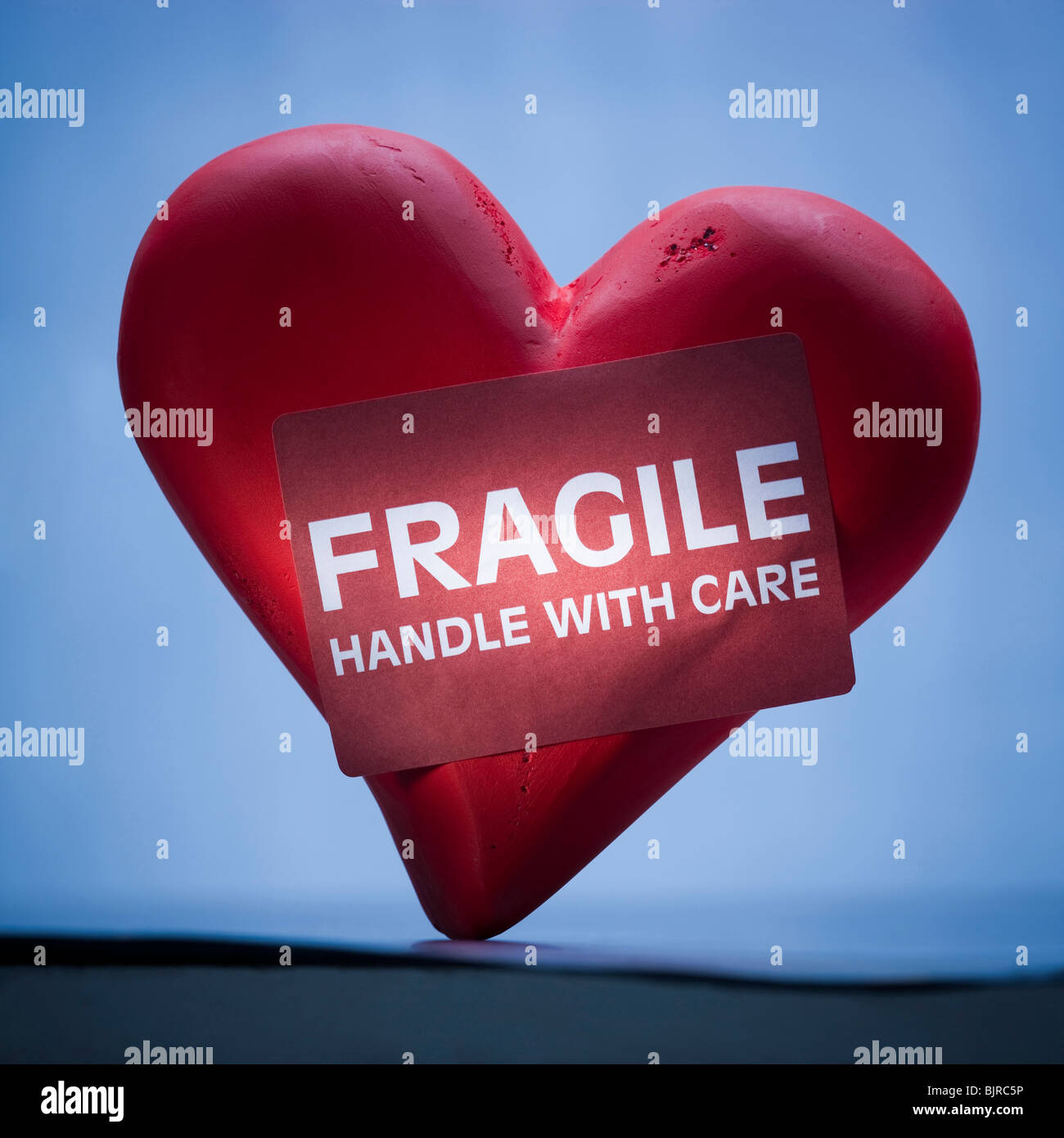 Heart with sign reading fragile - Stock Image