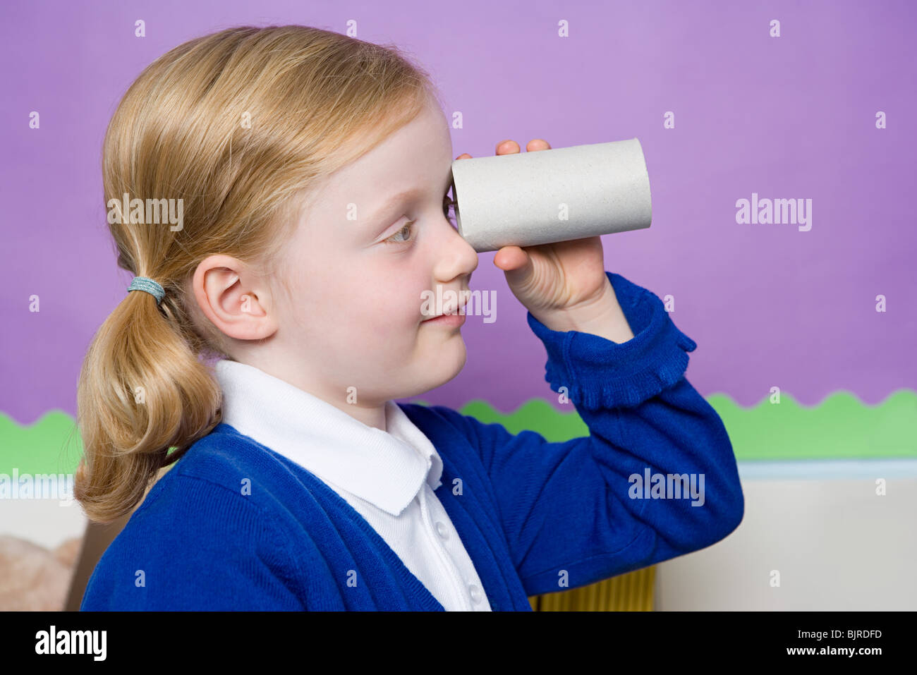 Girl looking through toilet roll Stock Photo