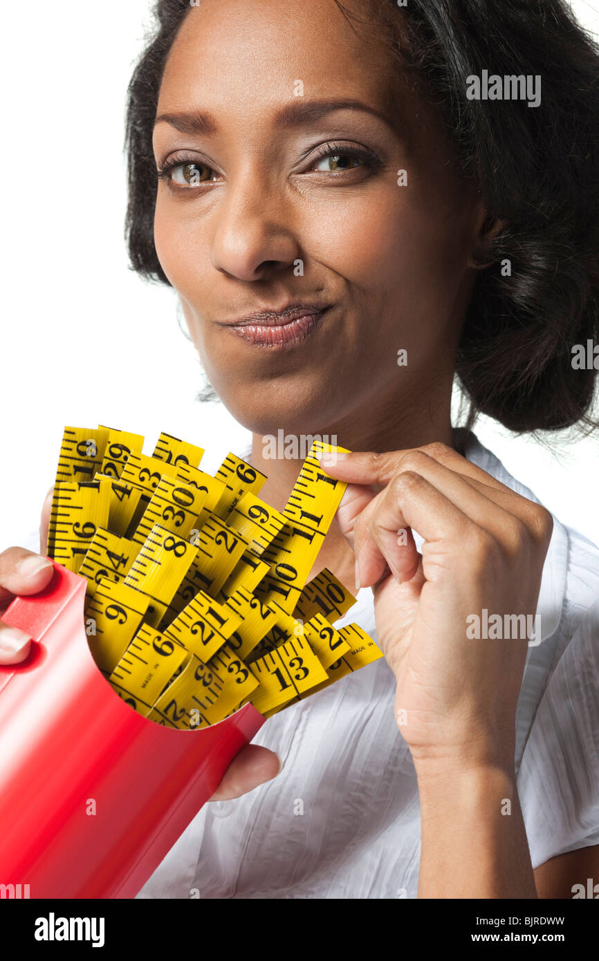 Mid adult woman holding container with mini tape measures instead of french fries - Stock Image