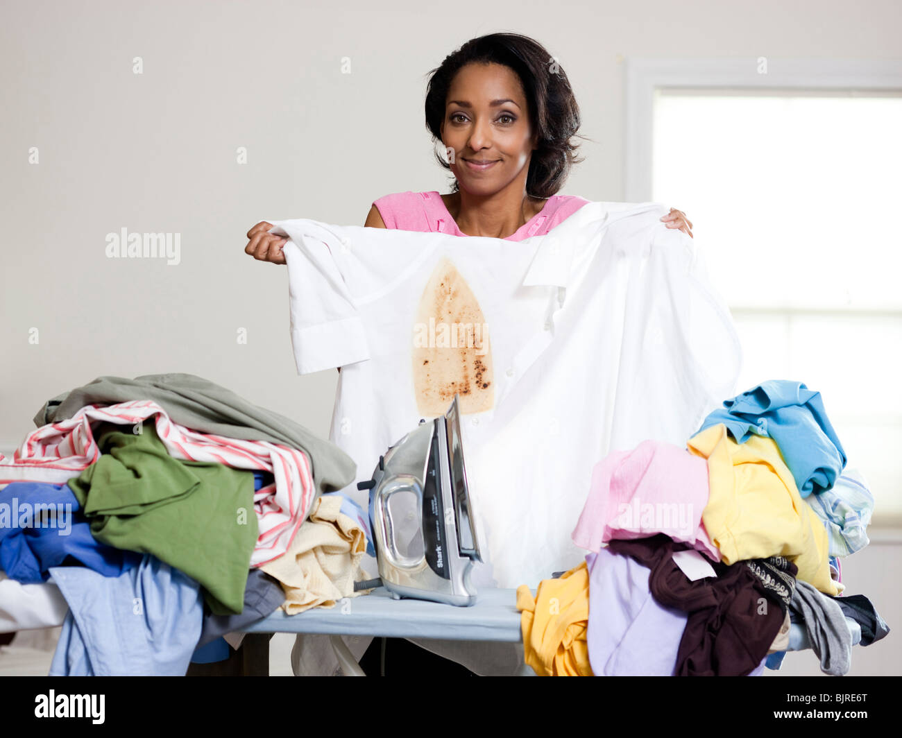 Orem, Utah, USA, mid adult woman holding burnt shirt - Stock Image