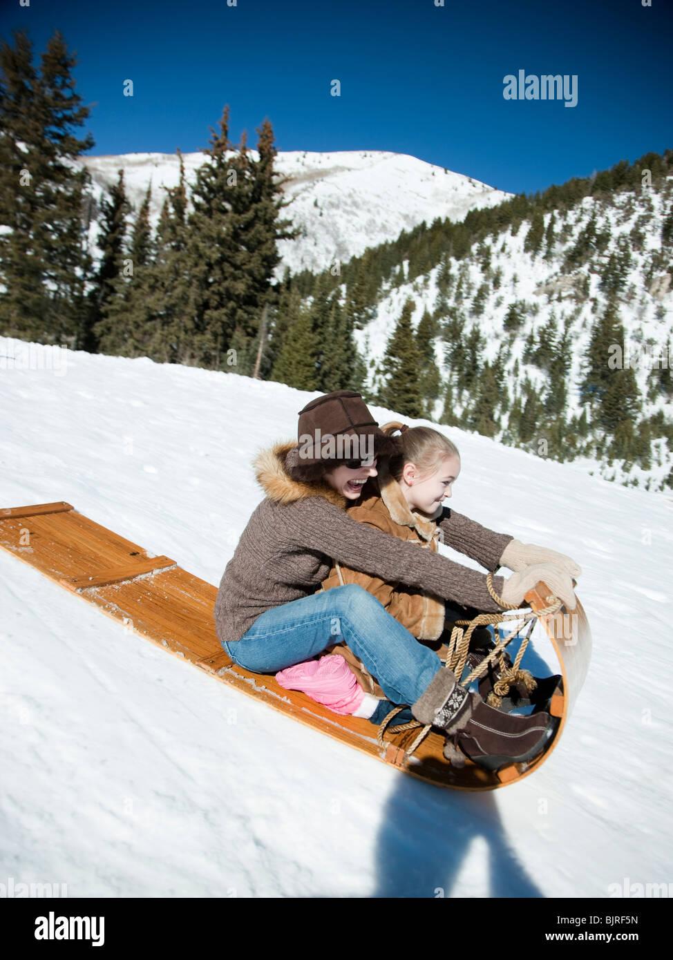 USA, Utah, Big Cottonwood Canyon, mother and daughter (8-9) tobogganing in mountains - Stock Image