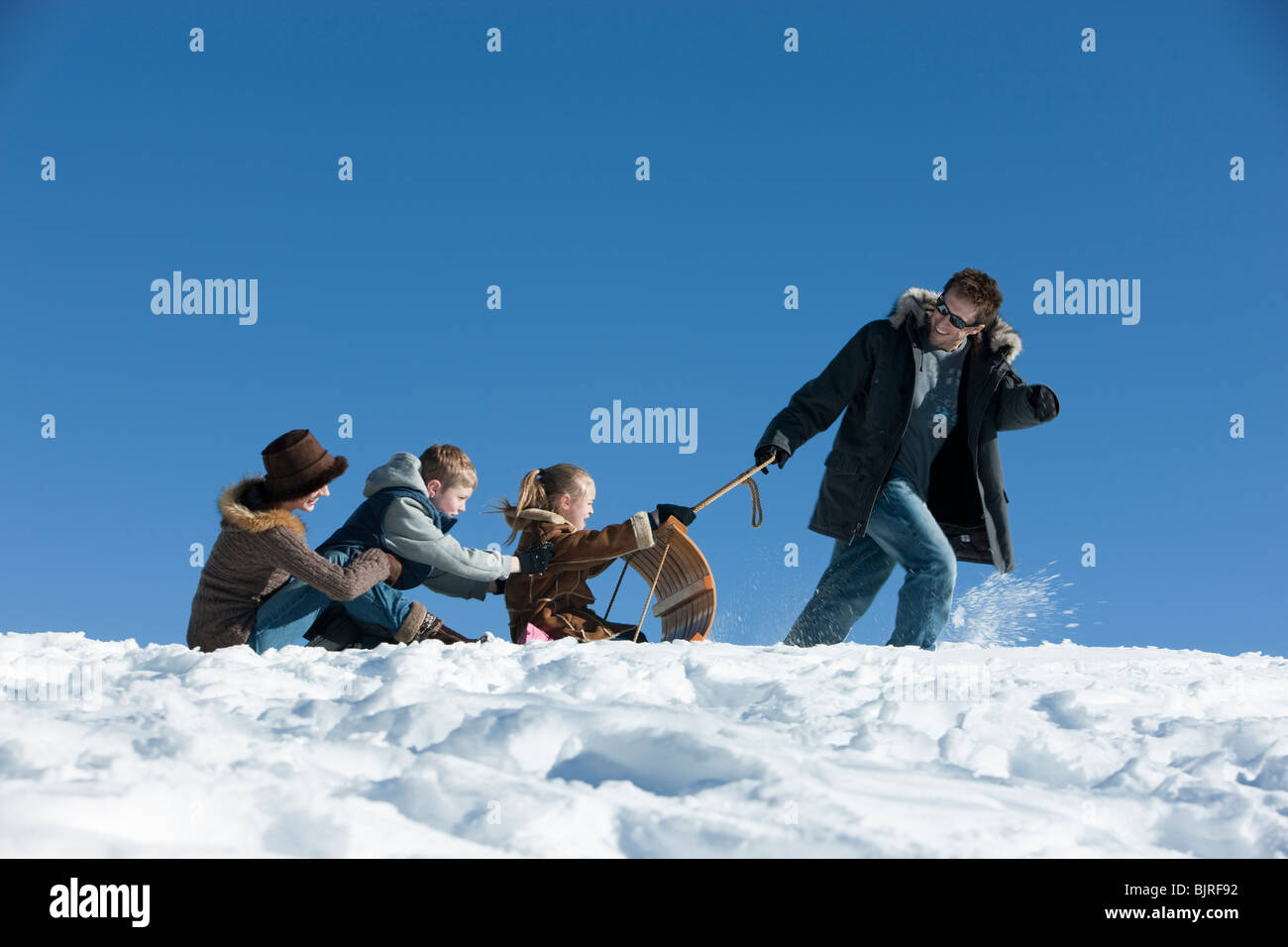 USA, Utah, Big Cottonwood Canyon, father pulling family on toboggan in mountains - Stock Image