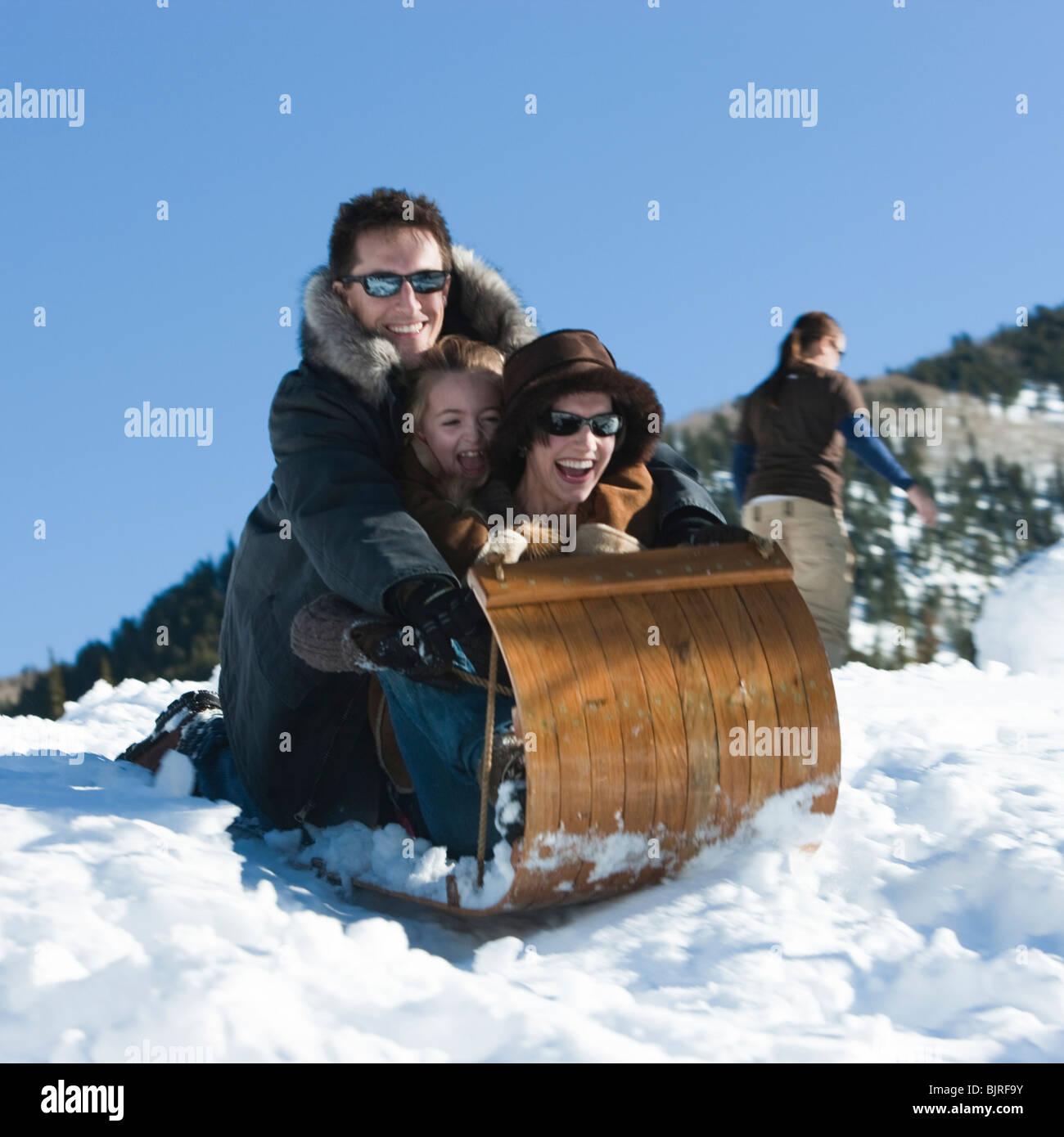 USA, Utah, Big Cottonwood Canyon, parents and daughter (8-9) tobogganing in mountains - Stock Image