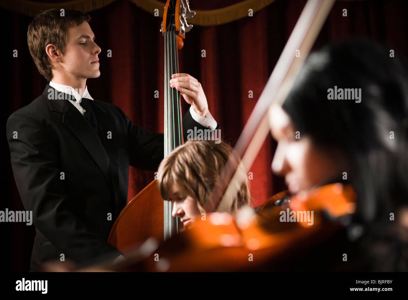 Three young musicians playing in orchestra - Stock Image
