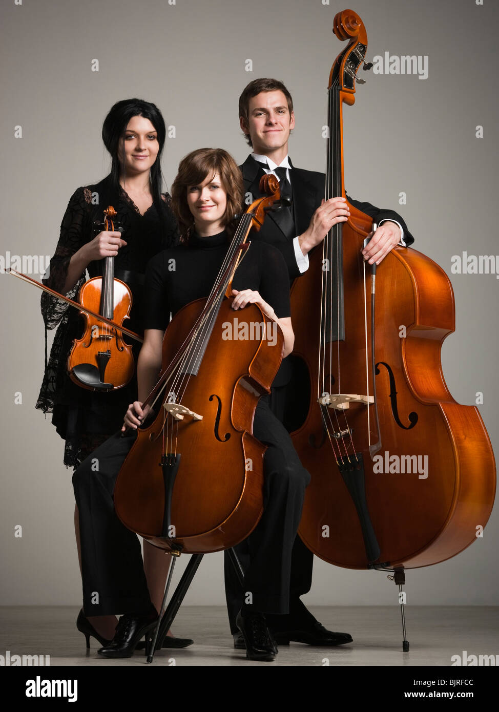 Studio portrait of three young musicians with instruments - Stock Image