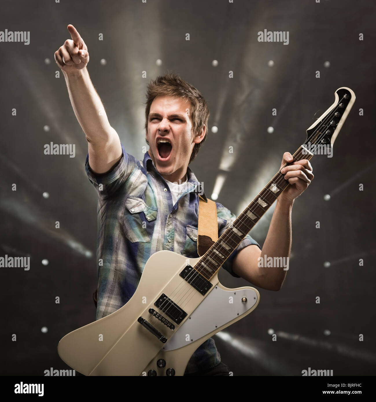 Young man playing bass guitar, studio shot - Stock Image