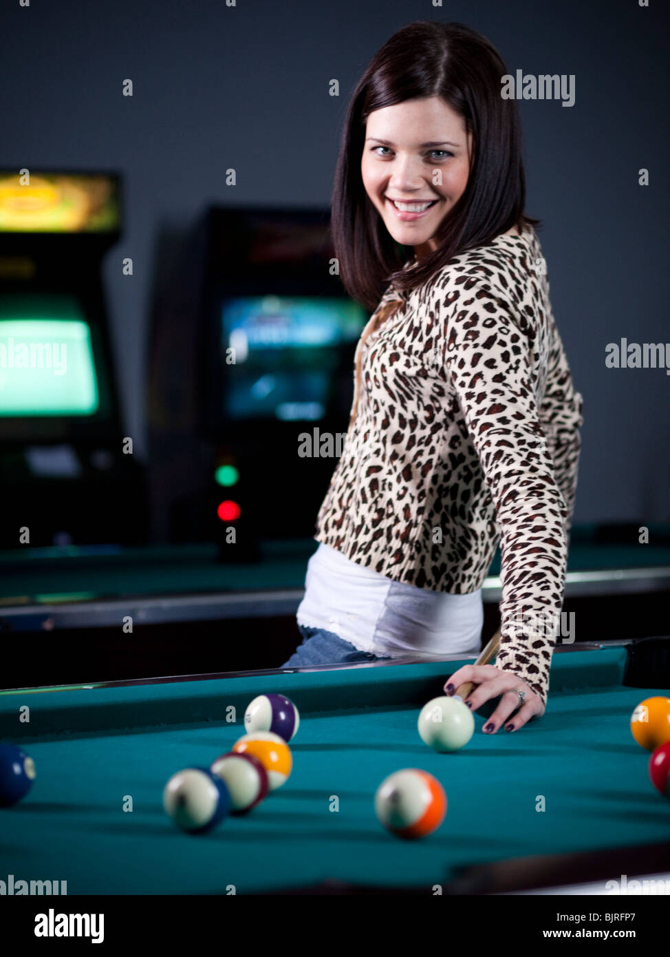 USA, Utah, American Fork, young woman standing in playroom with pool cue behind her back - Stock Image