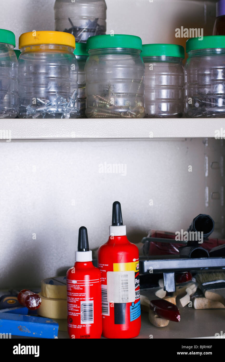 Tools, fasteners and hardware on the shelves of a cupboard in a home workshop. - Stock Image