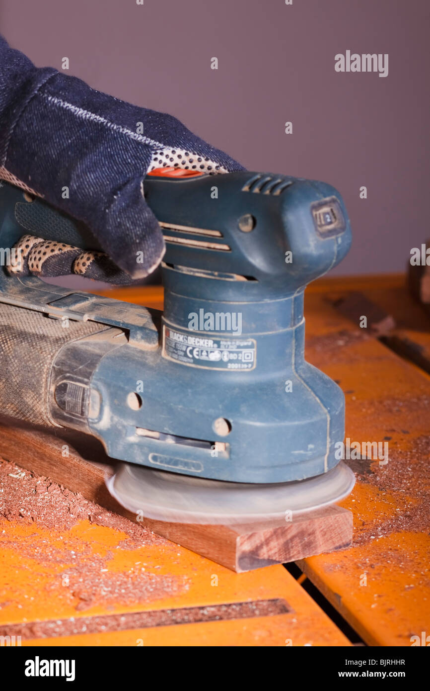 An orbital sander being used to finish a section of timber. Stock Photo
