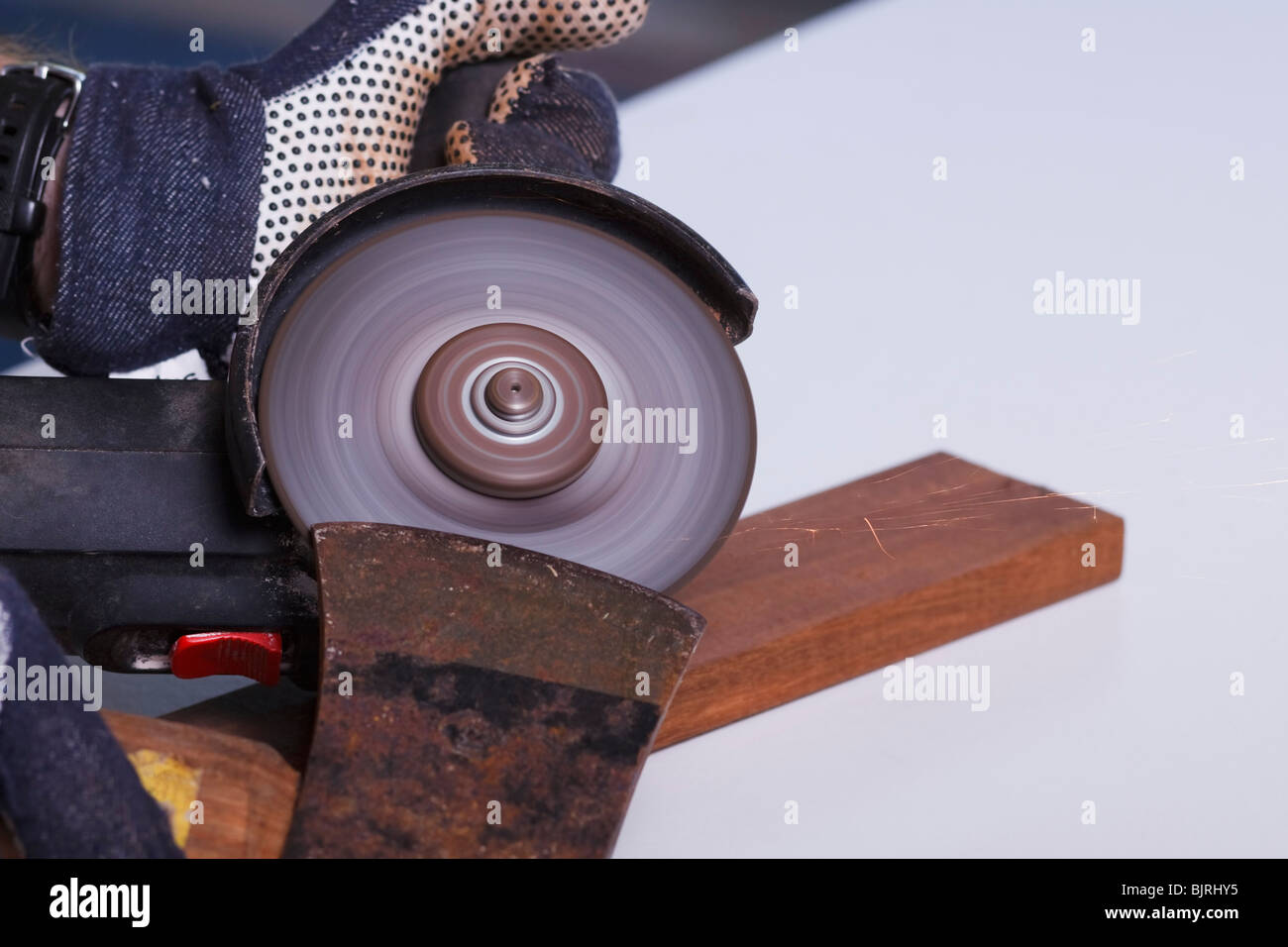 An angle grinder being used to sharpen the blade of an axe. - Stock Image