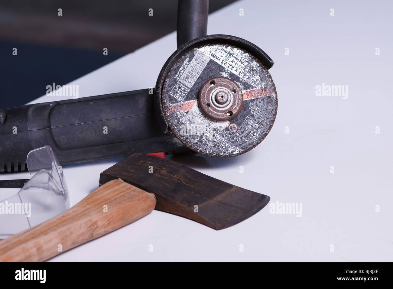 An angle grinder, axe and safety goggles. - Stock Image