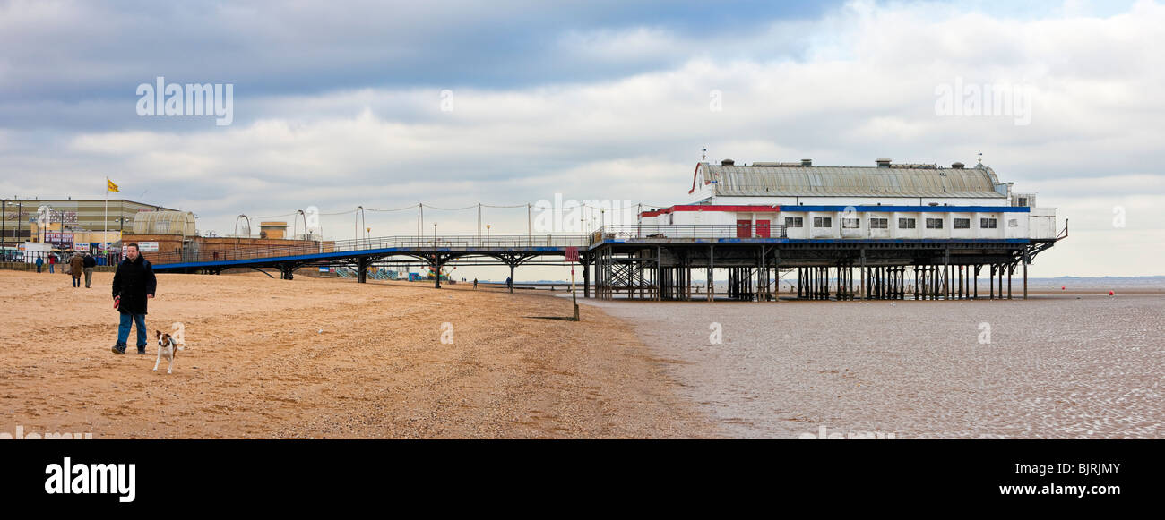 Man walks a dog along the beach near the Pier 39 on Cleethorpes beach, Lincolnshire England UK in winter - Stock Image