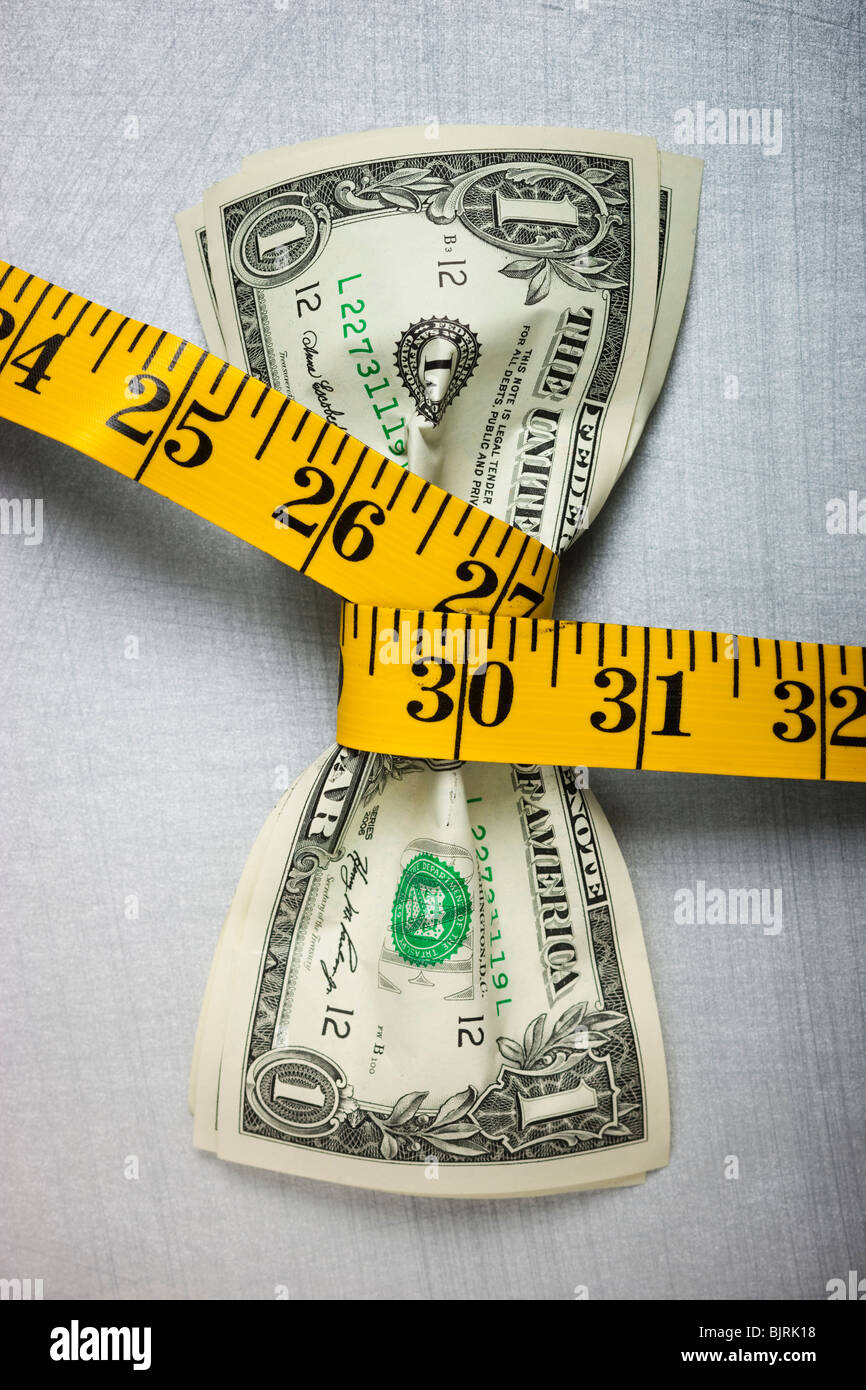 Studio shot of yellow measure tape squeezing two one dollar bills - Stock Image