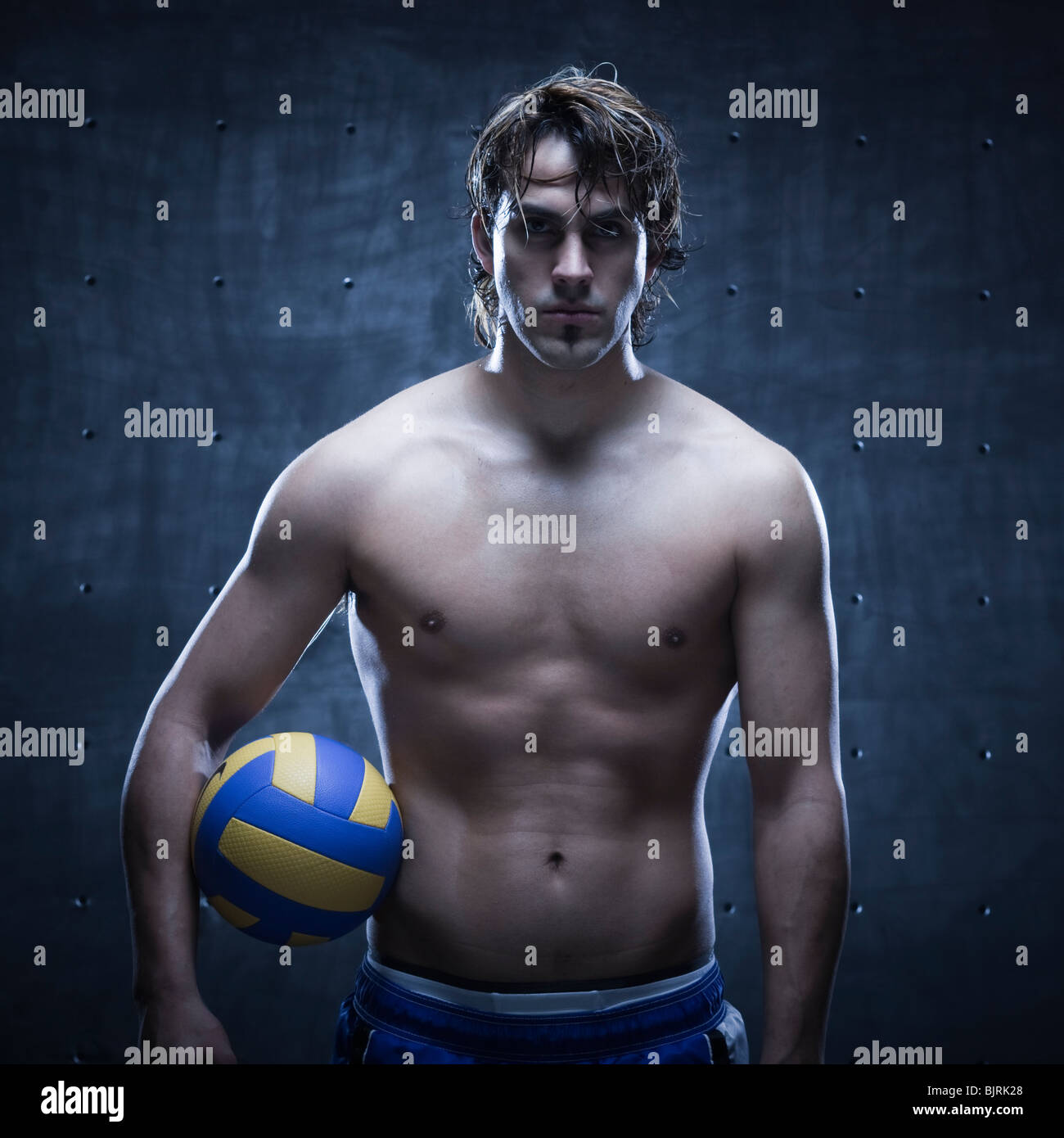 Studio shot of volleyball player standing and holding ball - Stock Image