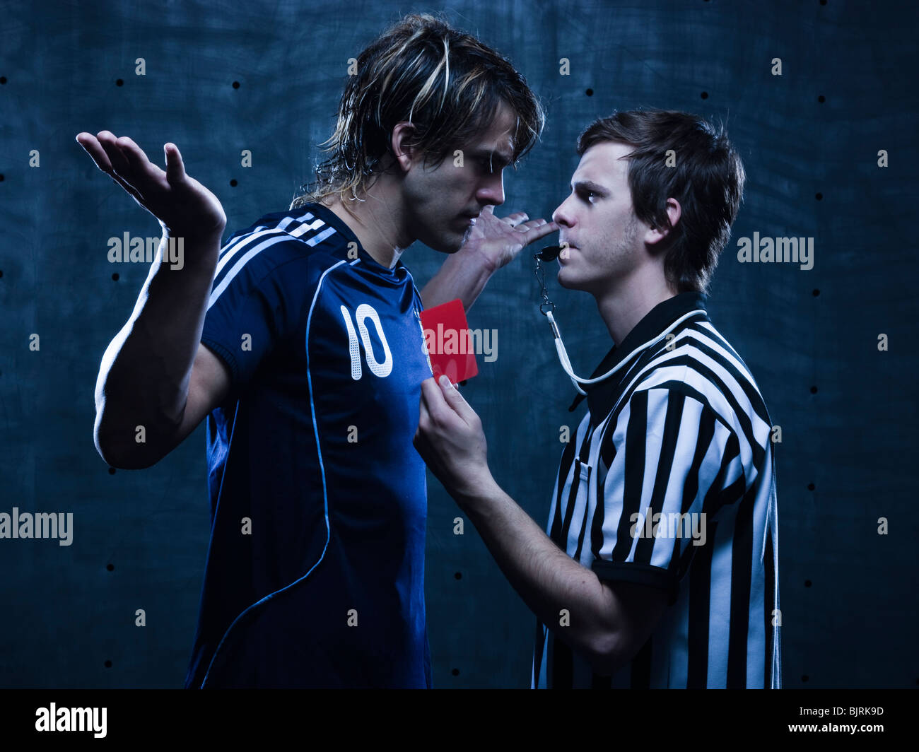 Studio shot of referee showing red card to soccer player - Stock Image