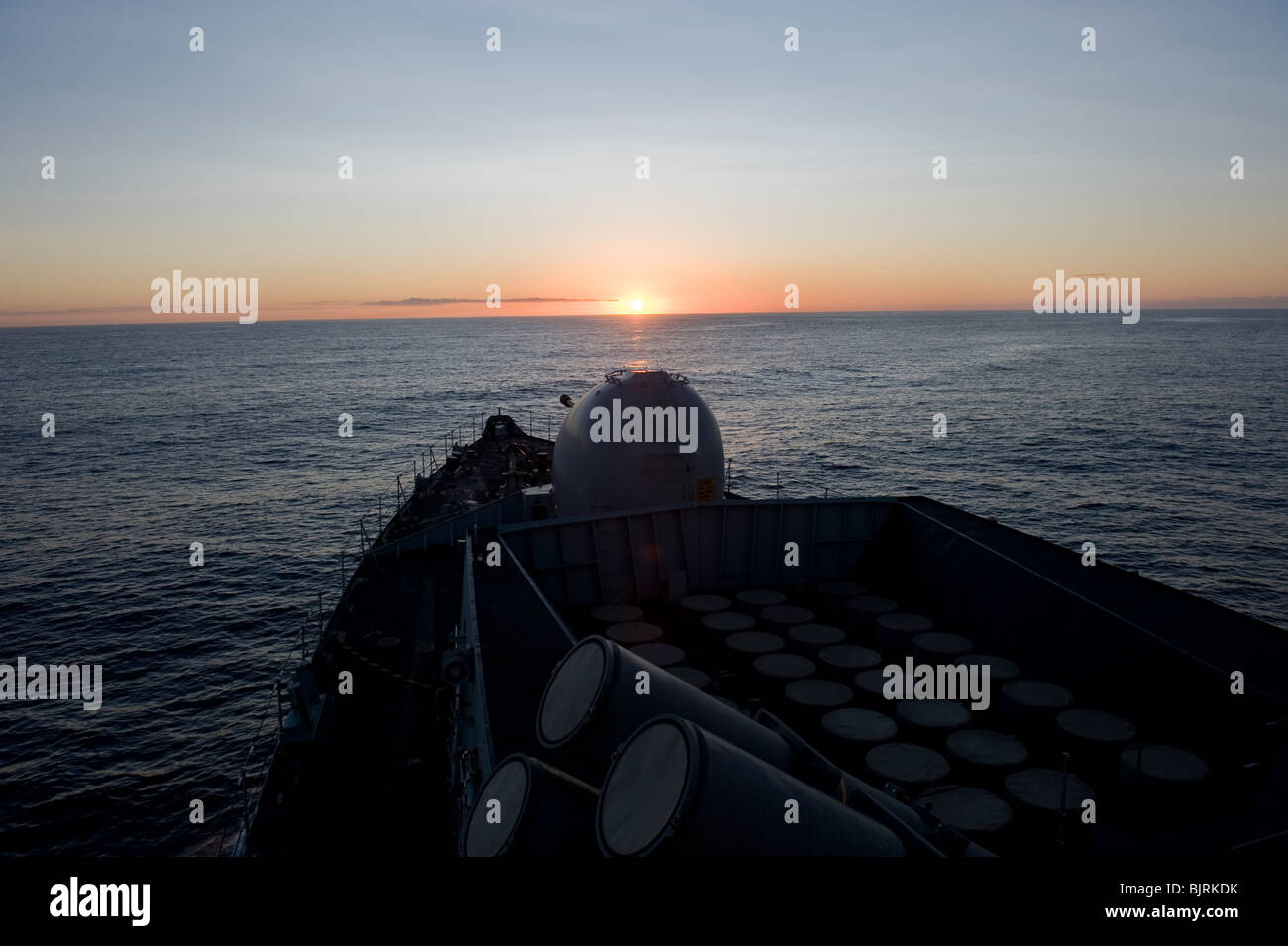 Bow of Royal Navy Type 23 frigate - sunset at sea - Stock Image
