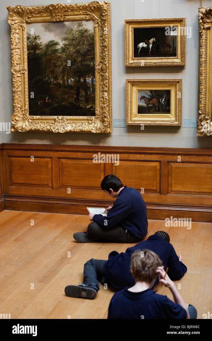 Schoolboys visitors to the Dulwich Picture Gallery appreciate classical framed paintings on the walls. - Stock Image