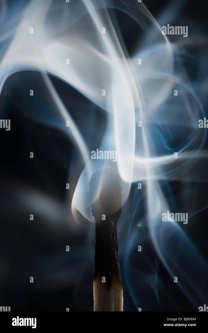 Smoking match against black background - Stock Image