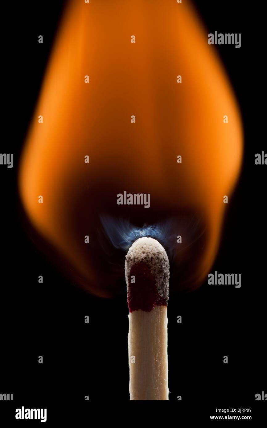 Burning match against black background - Stock Image