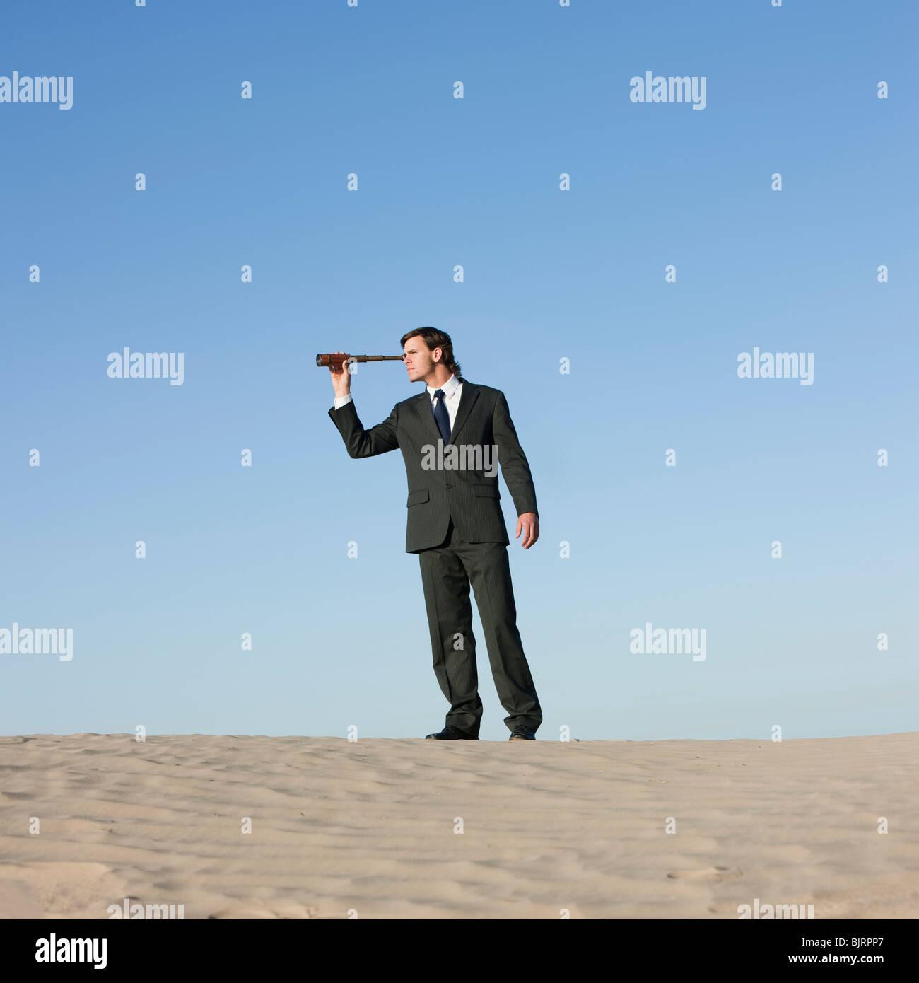 USA, Utah, Little Sahara, businessman looking through telescope in desert - Stock Image