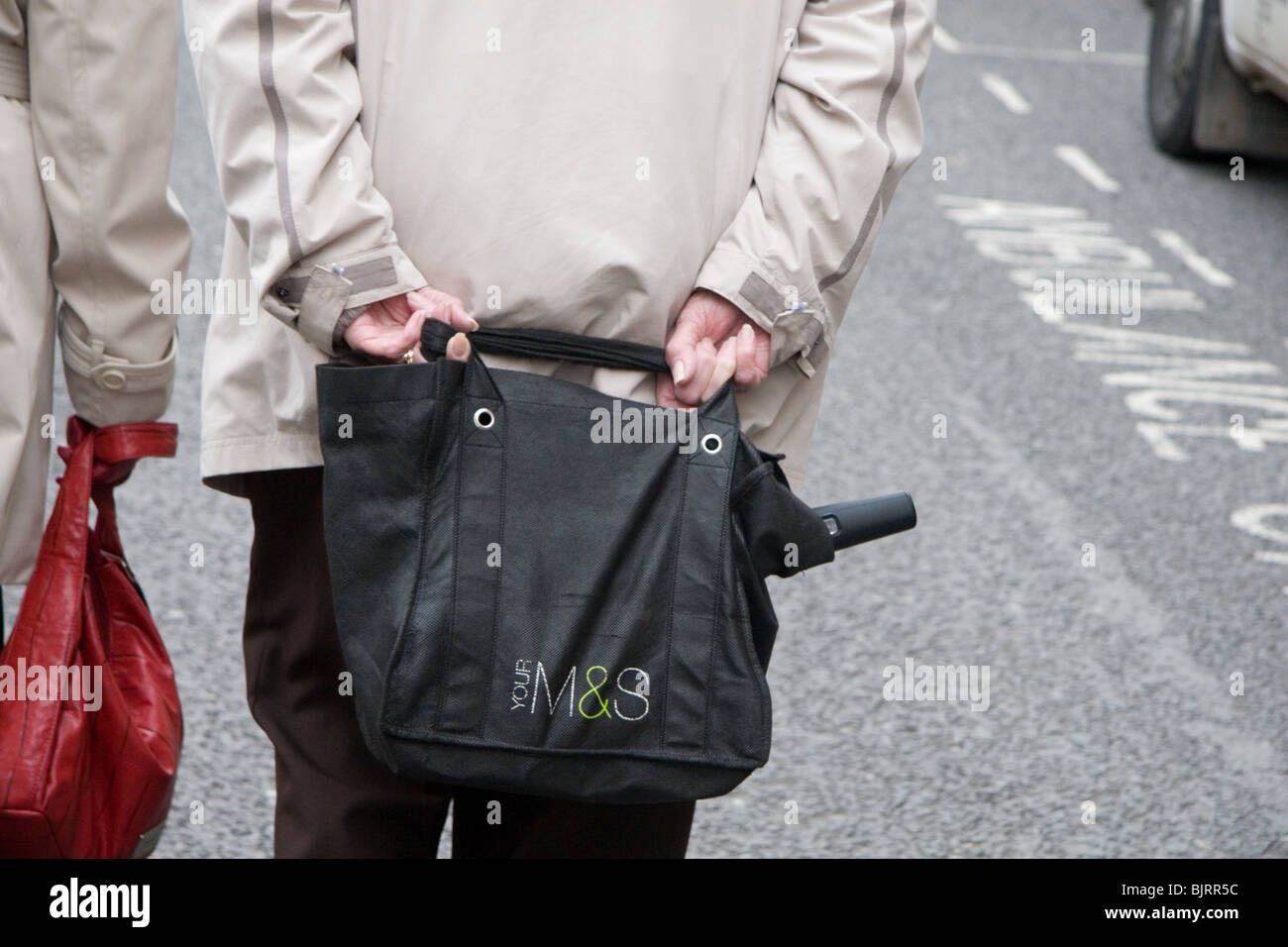 a4d7a0cd4f5b Close-up of an older woman carrying a Marks and Spencer shopping bag - Stock