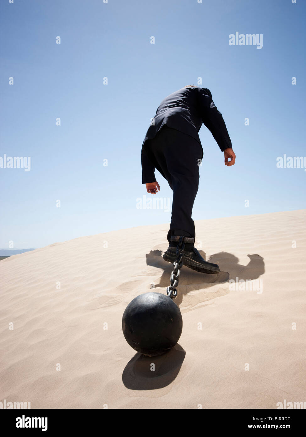 USA, Utah, Little Sahara, mid adult businessman pulling ball in chain on desert, rear view, low angle view - Stock Image
