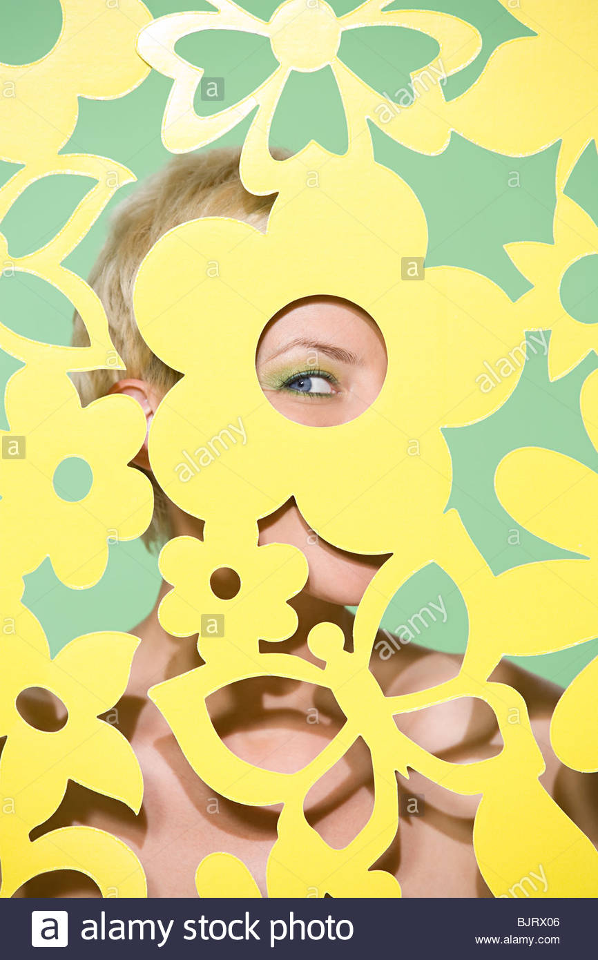 Woman peeking through cutout - Stock Image