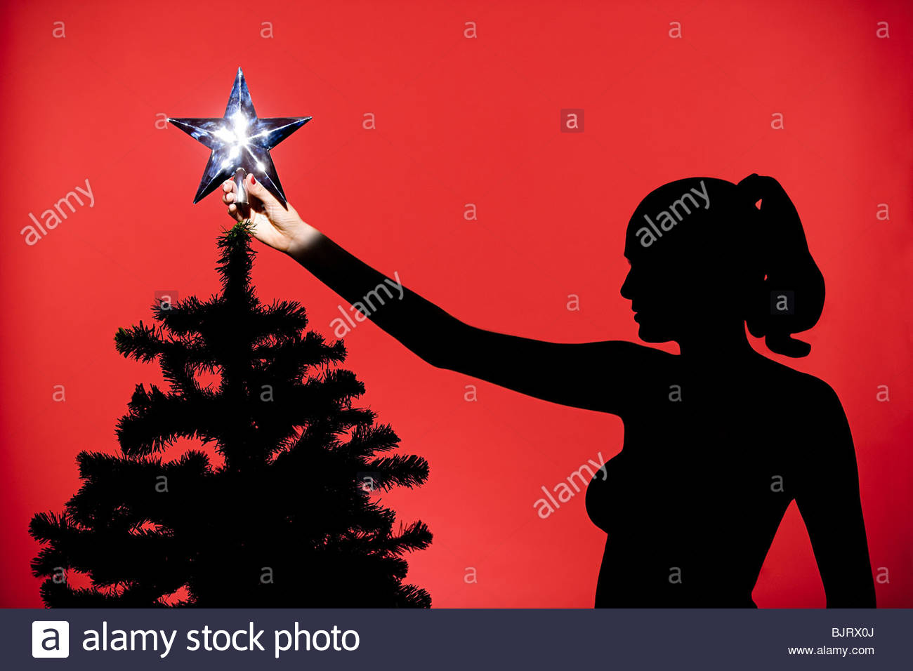 Woman putting star on christmas tree - Stock Image