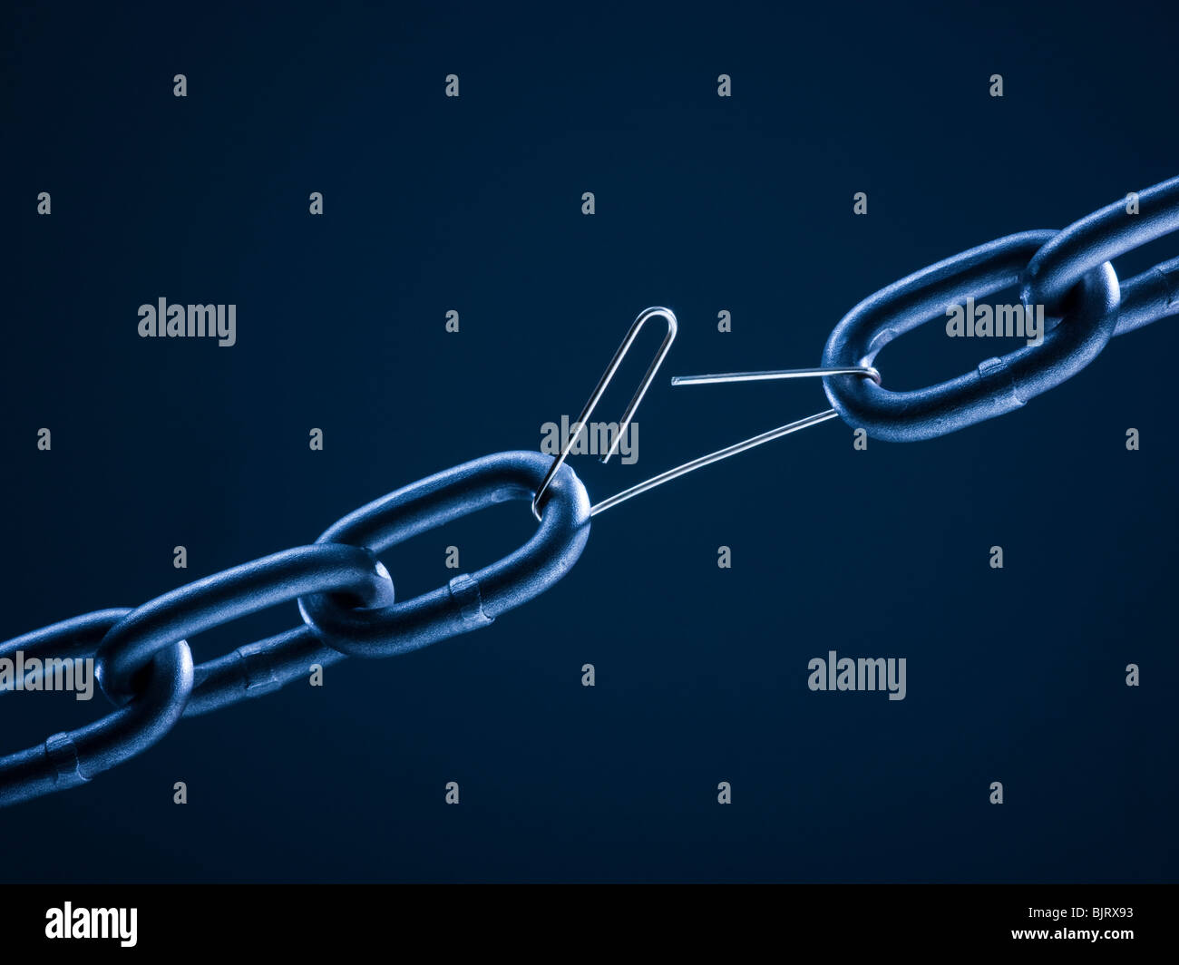 Chain linked with broken paper clip against blue background - Stock Image