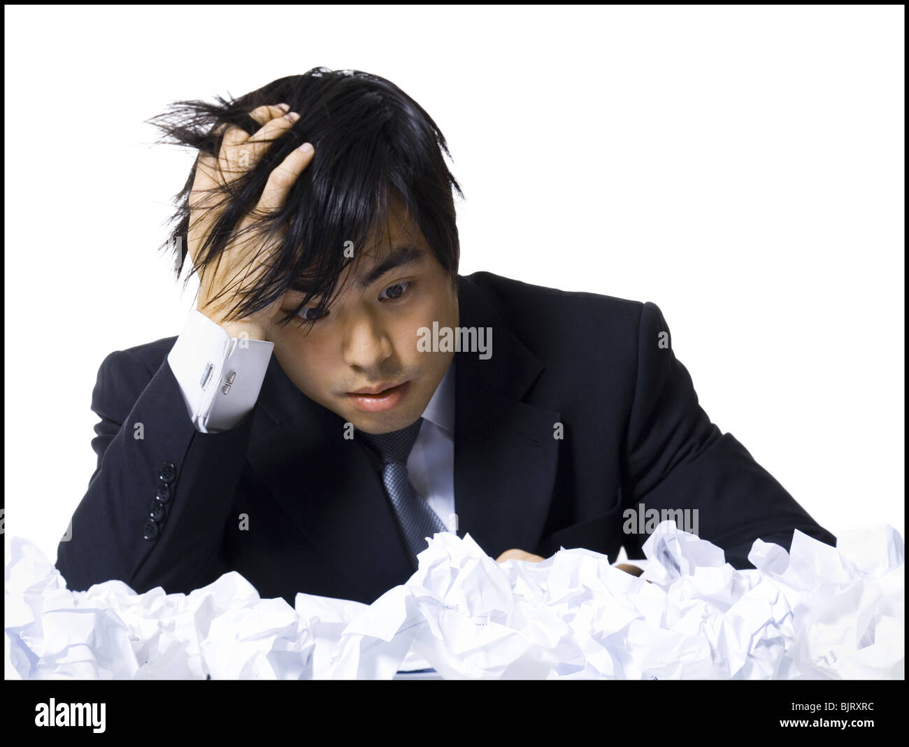 Frustrated businessman surrounded by crumpled papers - Stock Image