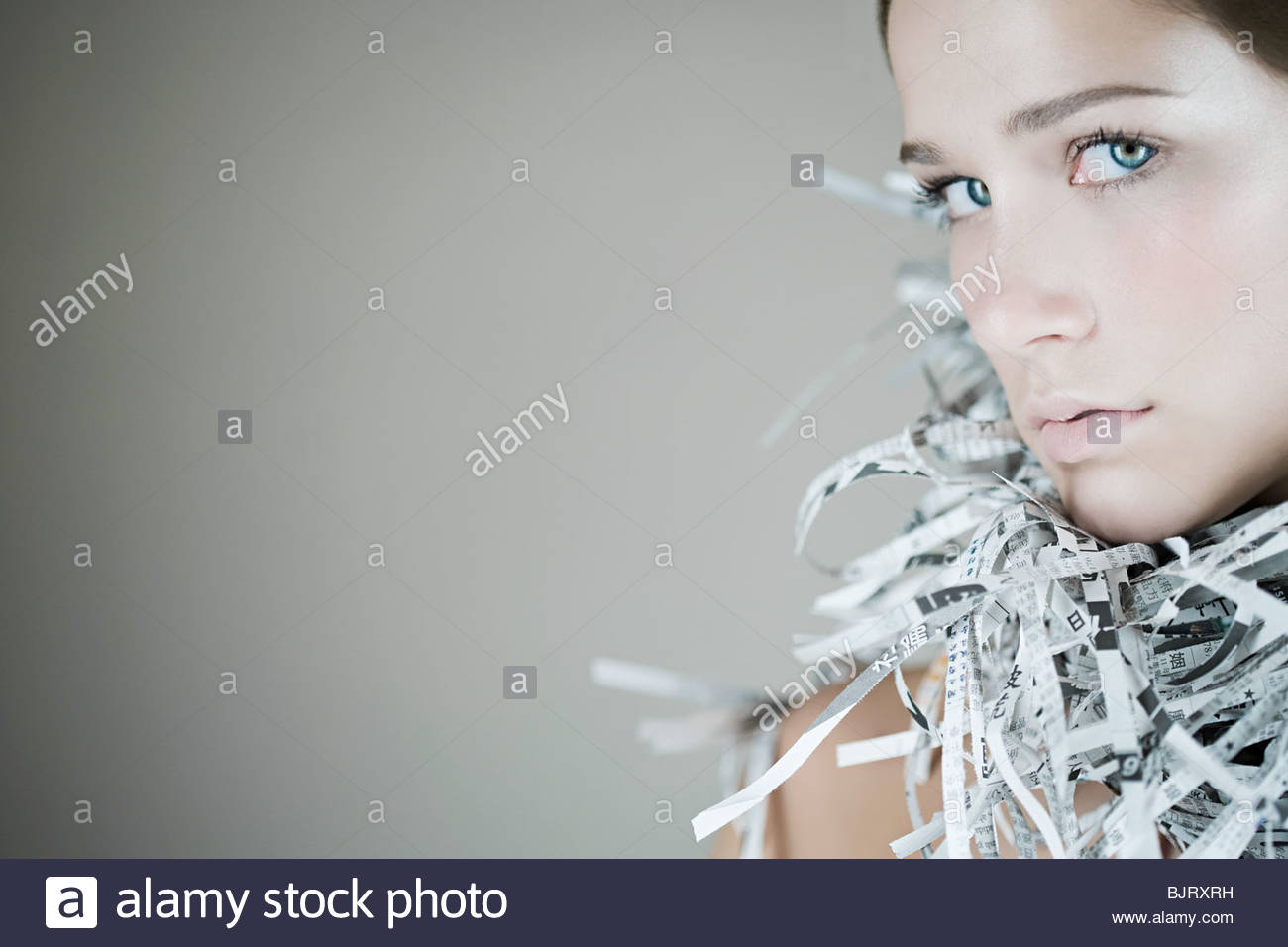 Portrait of a woman wearing a newspaper accessory - Stock Image