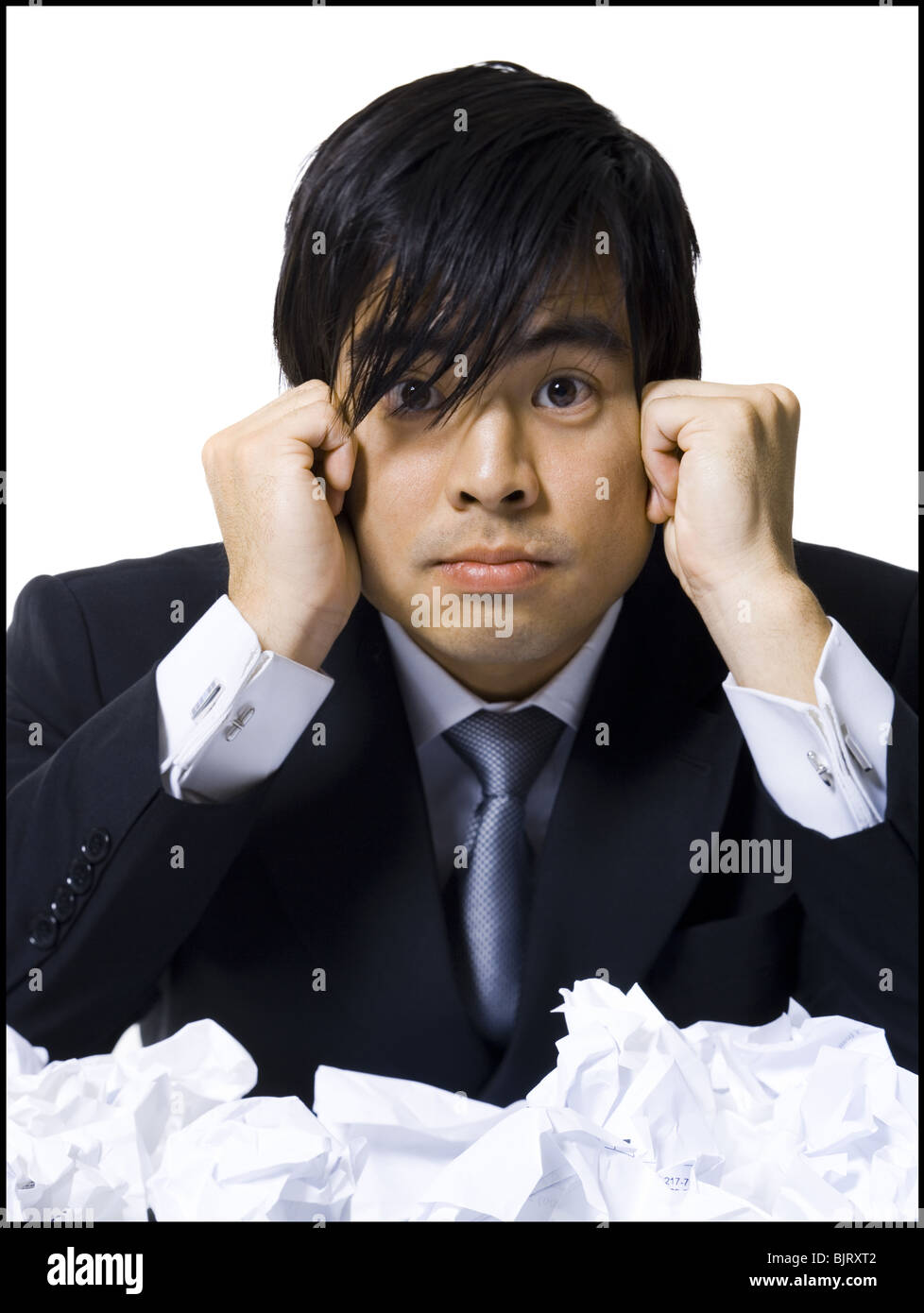 Frustrated businessman surrounded by crumpled papers Stock Photo