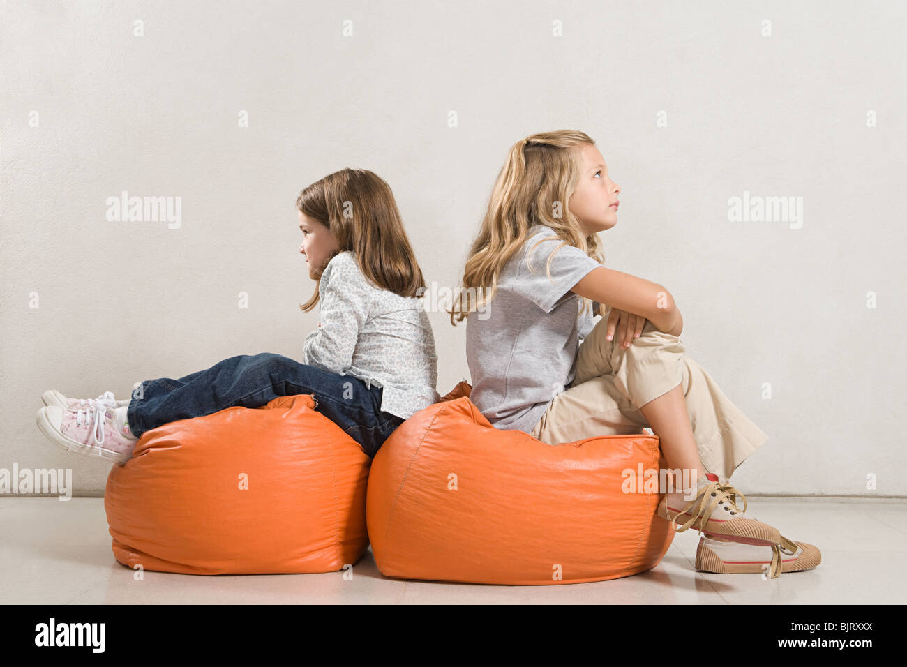 Sisters sat back to back on beanbags - Stock Image