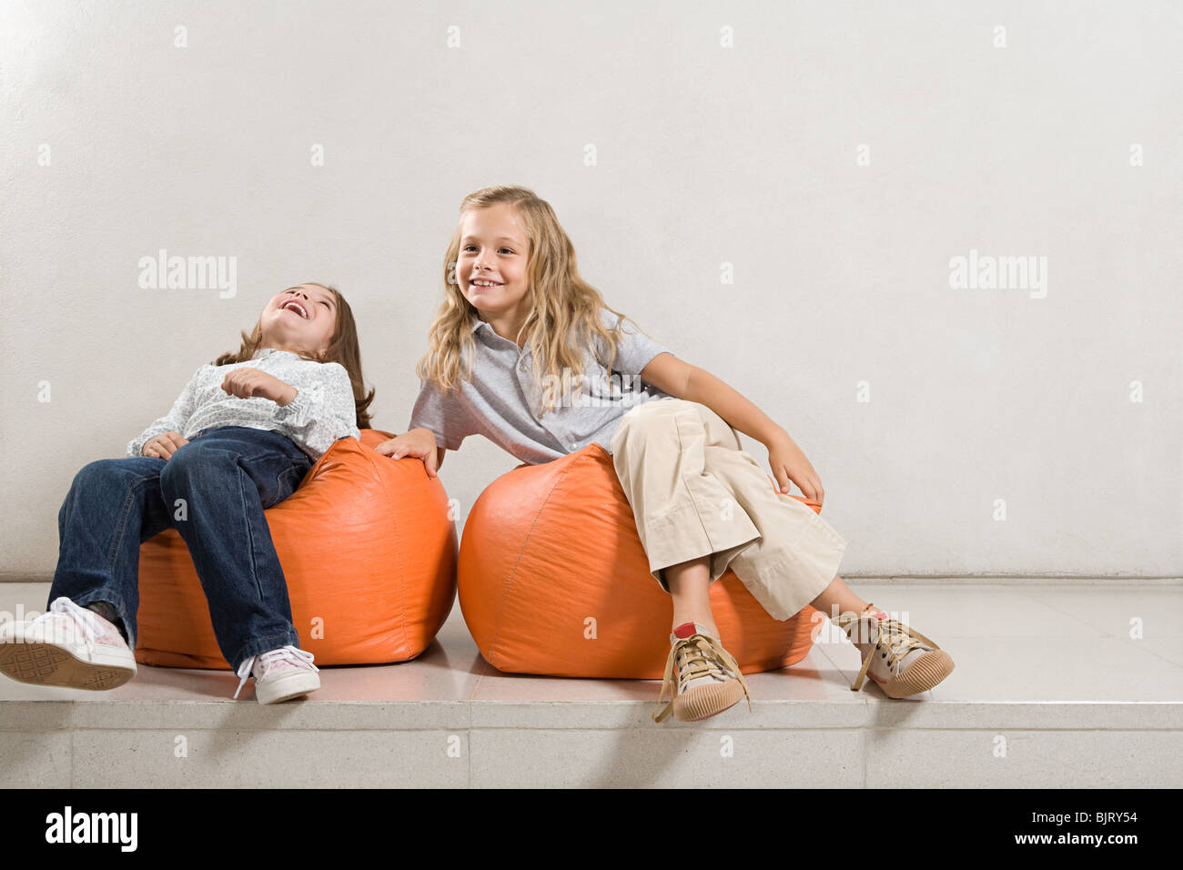 Sisters sat on bean bags - Stock Image