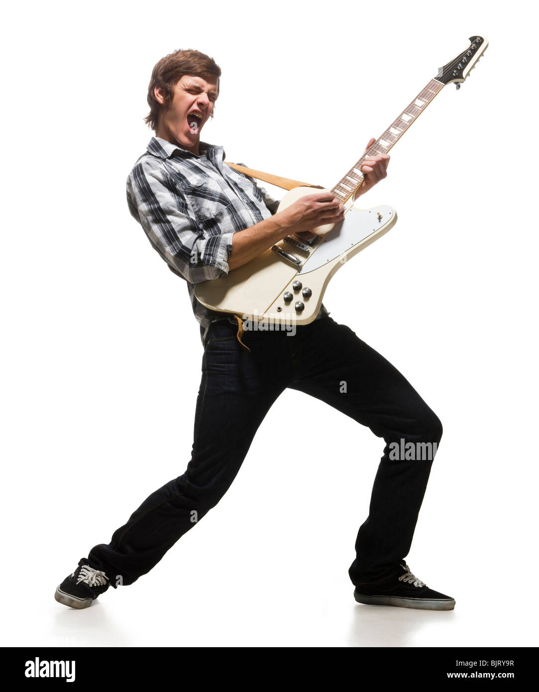 Young man playing electric guitar, shouting - Stock Image