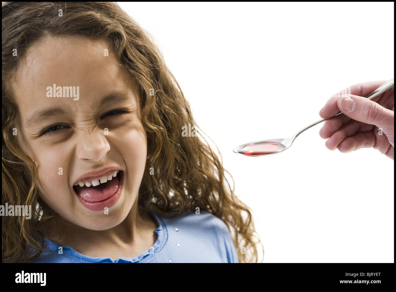 Young girl taking a spoonful of medicine - Stock Image