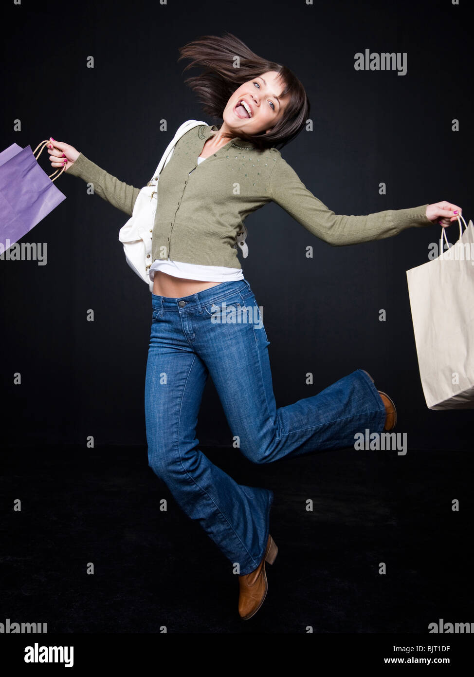 Young woman with shopping bags jumping, studio shot - Stock Image