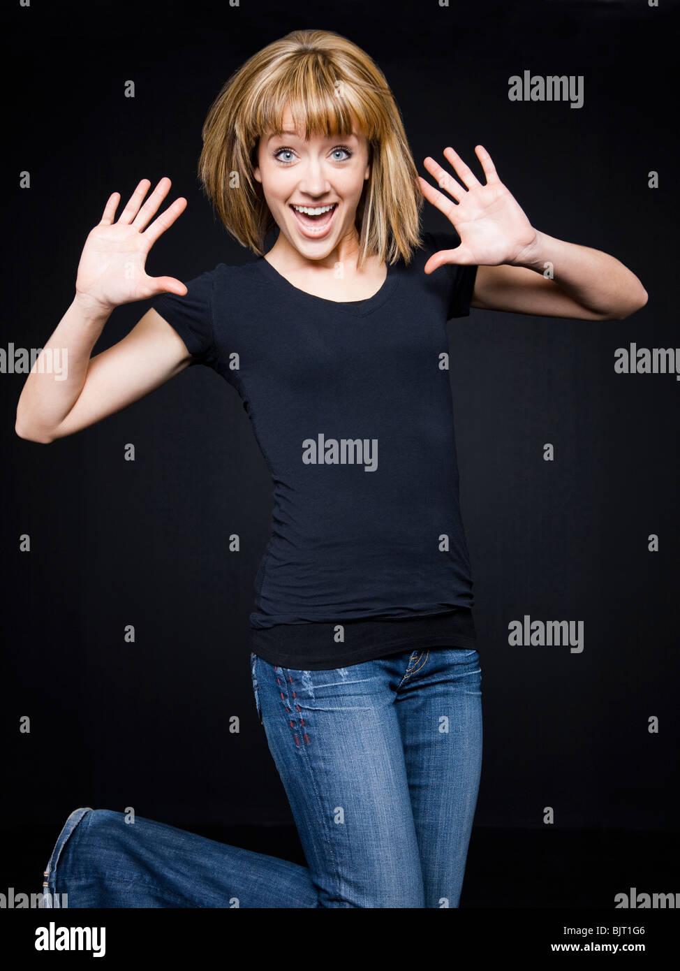 Young cheerful woman jumping, studio shot - Stock Image
