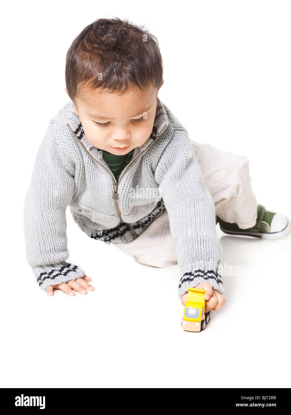 Studio shot of boy (18-23 months) playing with toy car - Stock Image