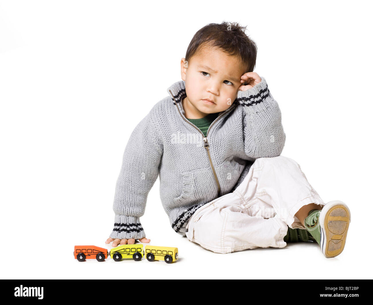 Studio portrait of boy (18-23 months) playing with toy car - Stock Image