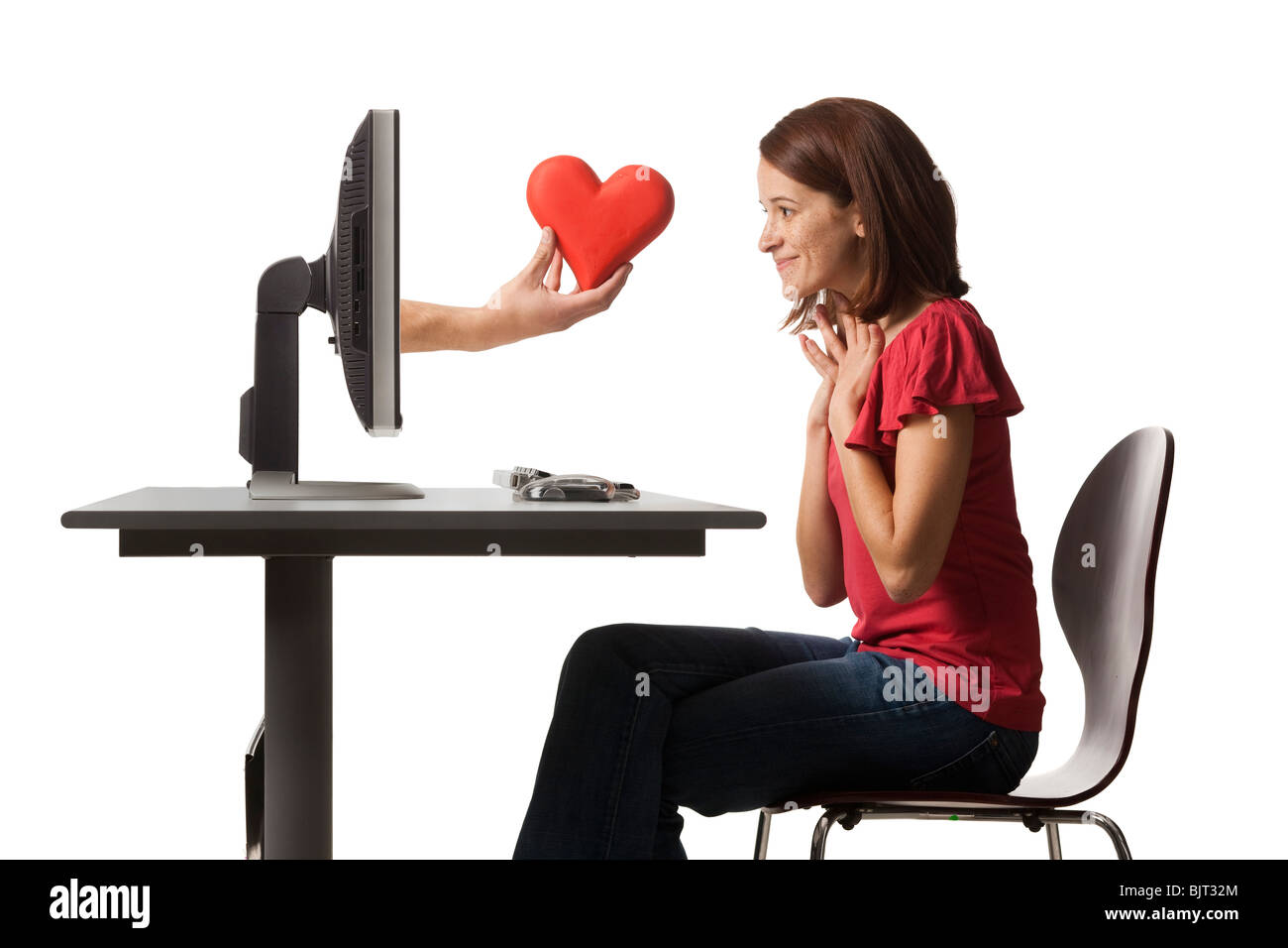 Conceptual picture of young woman receiving red heart out of her computer - Stock Image