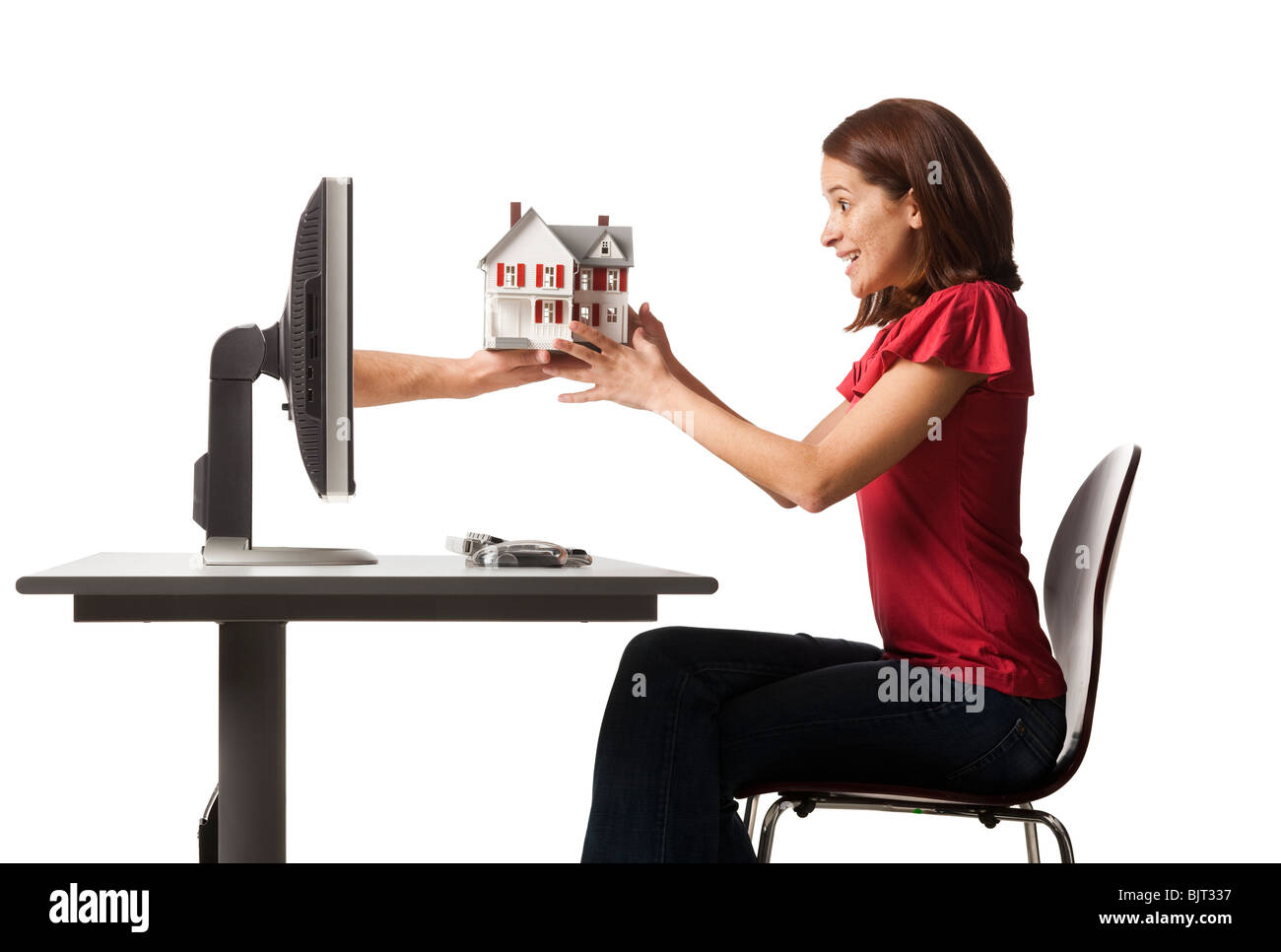 Conceptual picture of young woman receiving house out of her computer - Stock Image