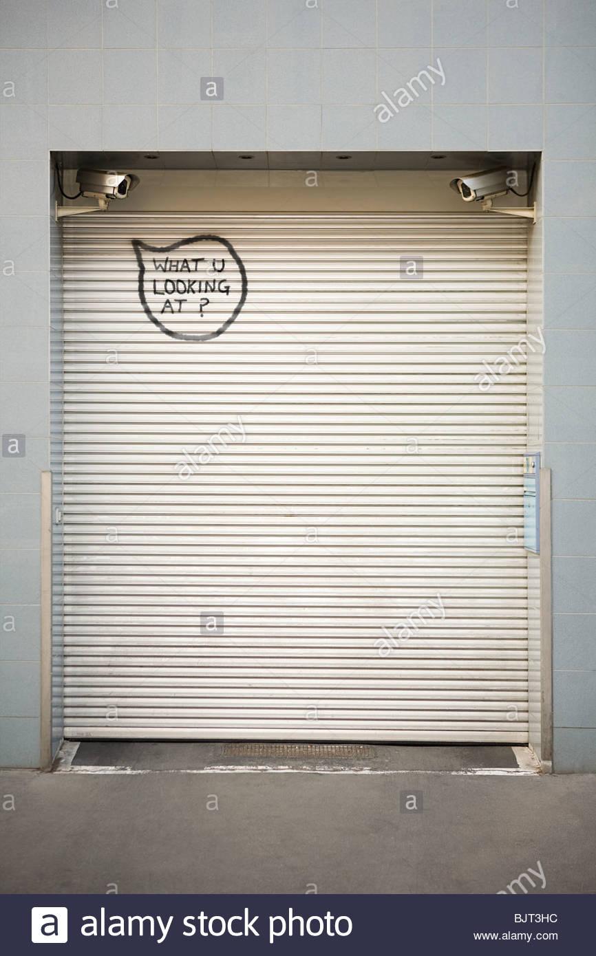 Graffiti written on a shutter - Stock Image